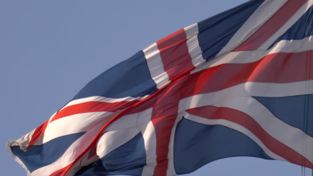 a close-up of the union jack flag flying - politics icon stock videos & royalty-free footage