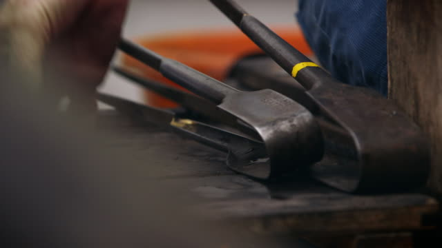 close-up of tools and a smoking pad being moved around on a glassblower's bench. - heat stock videos & royalty-free footage