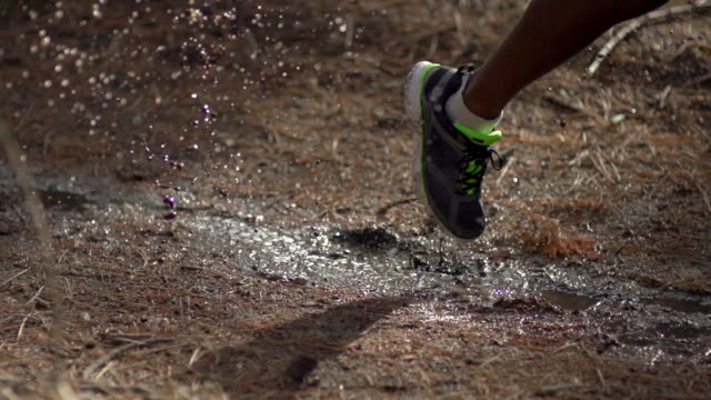 close-up of trail runners shoe as he runs through a mud puddle in a forest. - super slow motion - filmed at 240 fps - mud stock videos & royalty-free footage