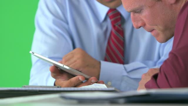 vídeos y material grabado en eventos de stock de close-up of two businessmen working with tablet on greenscreen - vestimenta de negocios formal