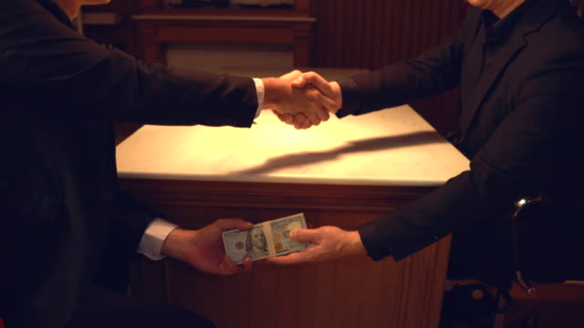 close-up of two businesspeople shaking hand and taking bribe under wooden table.hands passing money under table corruption bribery. - antigienico video stock e b–roll