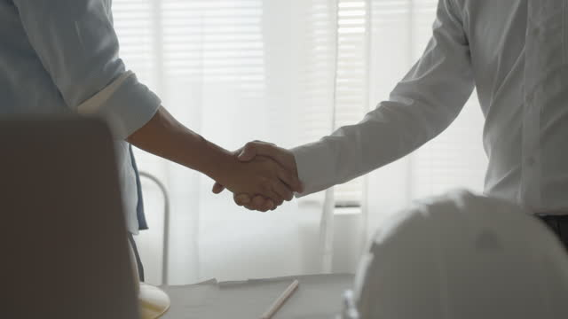 vídeos de stock e filmes b-roll de close-up of two businesspeople shaking hands together in office - parceria