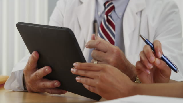 closeup of two doctors using a tablet in the office - 医療機器点の映像素材/bロール