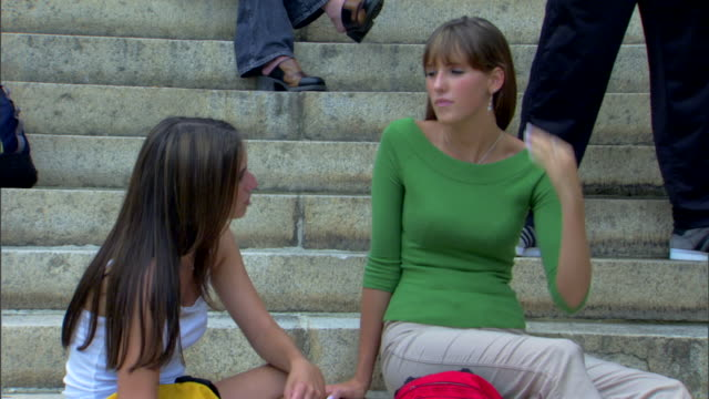 close-up of two girls sitting on the stairs talking. - only teenage girls stock videos & royalty-free footage