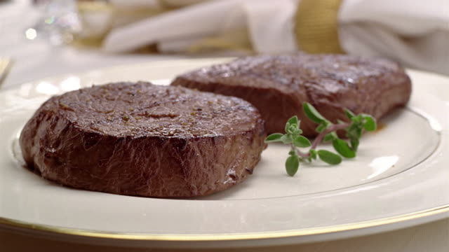 close-up of two grilled sirloin steaks on a plate with a spring of garnish. - garnish stock videos & royalty-free footage