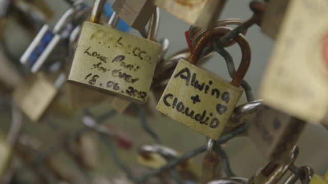 Close-up of two padlocks chained to the Pont des Arts bridge in Paris display love messages from visitors, 2013.