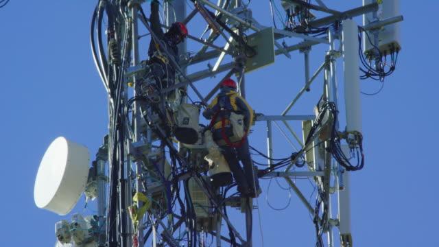 närbild av två tekniker montering en ny 5g mobiltelefon tower på en klar, solig dag - radio och tv utsändning bildbanksvideor och videomaterial från bakom kulisserna
