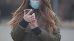 Close-up of unrecognizable young woman in protective mask using smartphone. Brunette woman standing on city street reading news about coronavirus. Medicine, healthcare, hazard.