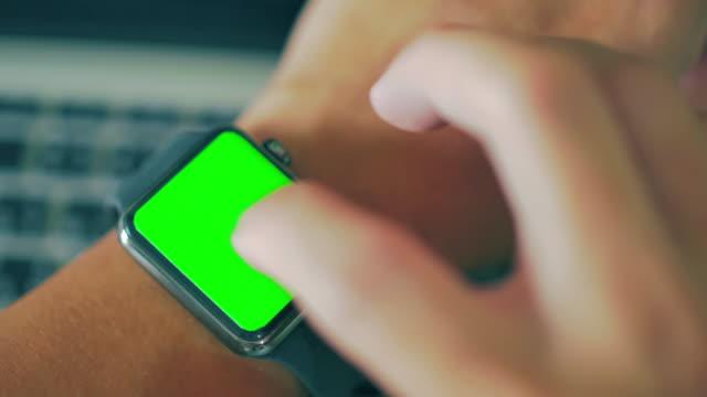 stockvideo's en b-roll-footage met close-up van het gebruik van slimme horloge, groen scherm - wijzerplaat