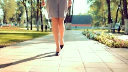 Close-up of walking girls legs in the park