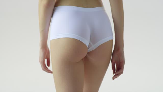 nahaufnahme des hinternden frauen in weißer unterwäsche. - hüfte stock-videos und b-roll-filmmaterial