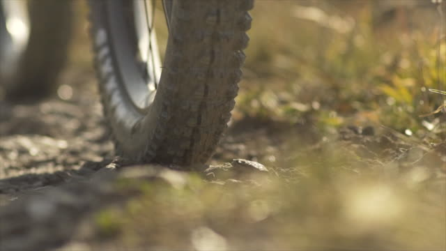 Closeup of wheels and tires on a mountain bike trail. - Slow Motion