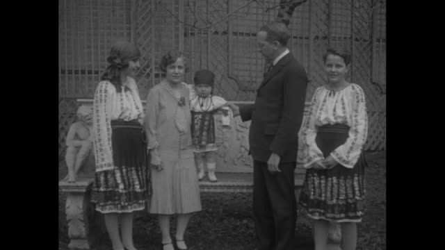 vídeos de stock, filmes e b-roll de closeup of william smith culbertson us envoy to romania he poses with girls in native romanian clothing and mrs culbertson / at a train station a... - moving activity