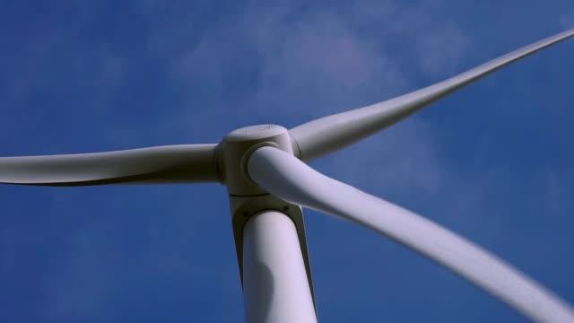 vídeos y material grabado en eventos de stock de close-up de palas de rotor de turbina de viento girando contra fondo de cielo azul - huella de carbono