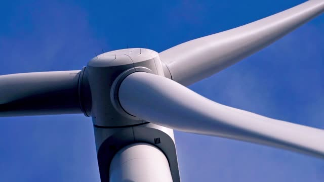 close-up of wind turbine rotor blades spinning against blue sky background - carbon footprint stock videos and b-roll footage