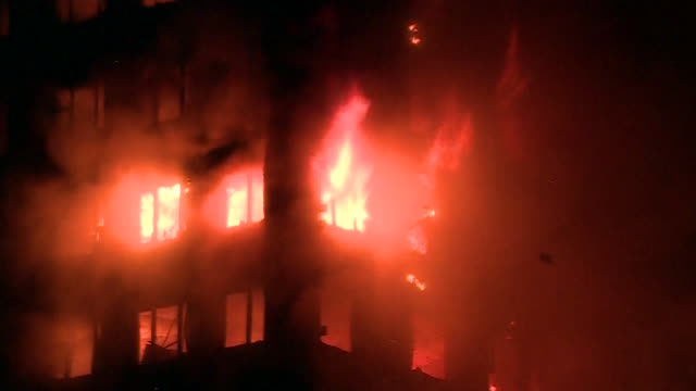 vidéos et rushes de closeup of windows during the grenfell tower fire at night - brasier