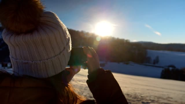 vídeos de stock e filmes b-roll de close-up of winter traveler at sunset using camera, close up of one young woman tourist taking photos, photographing, enjoying the winter mountain, portrait, winter sport, travel, exploration, adventure, tourism, outdoors, mountain hiking, - fotógrafo