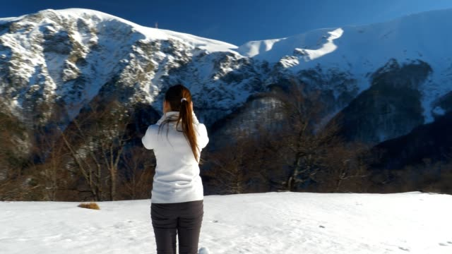 Close-Up of Winter Traveler at Sunset Using Camera, Close Up of One Young Woman Tourist Taking Photos, Photographing, Enjoying the Winter Mountain, Portrait, Winter Sport, Travel, Exploration, Adventure, Tourism, Outdoors, Mountain Hiking,