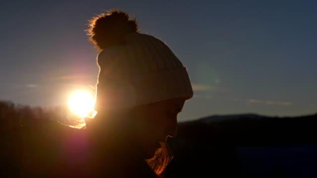 vídeos de stock, filmes e b-roll de close-up do viajante do inverno no por do sol usando o smartphone, feche acima de um turista da mulher nova usando o internet, conversando, apreciando a montanha do inverno, retrato, esporte de inverno, curso, exploração, aventura, turismo, ao ar livre,  - back lit