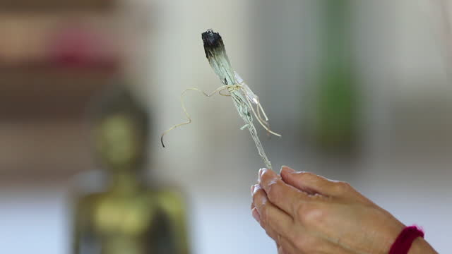 close-up of woman blowing on incense as part of new age ceremony - new age stock-videos und b-roll-filmmaterial