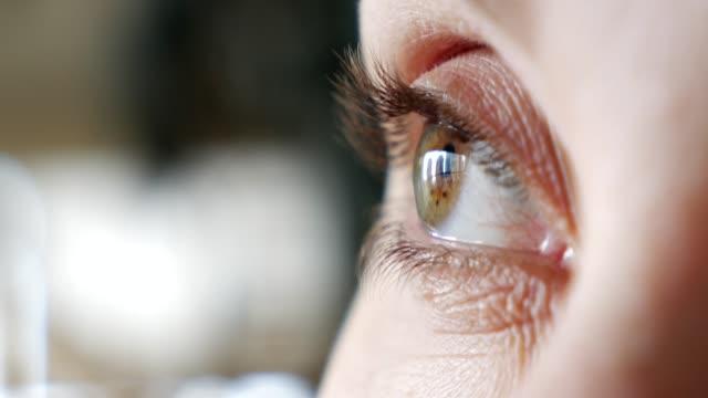 close-up of woman eyes - curiosità video stock e b–roll