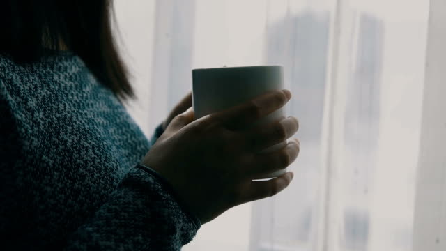 close-up of woman holding a coffee near window - morning stock videos & royalty-free footage