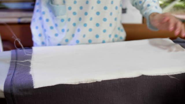 Nahaufnahme von Frau Kleidung mit einem dampfenden Eisen Bügeln