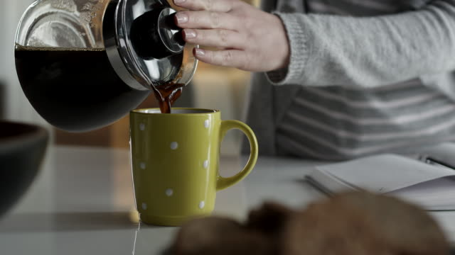 Close-up of woman pouring coffee