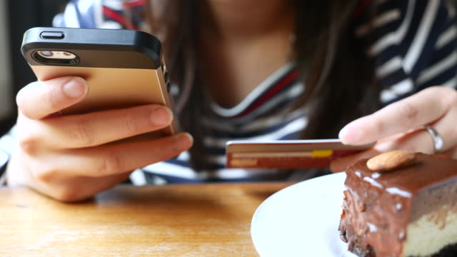 Close-up of woman shopping online on Mobile phone with chocolate cake, 4K(UHD)