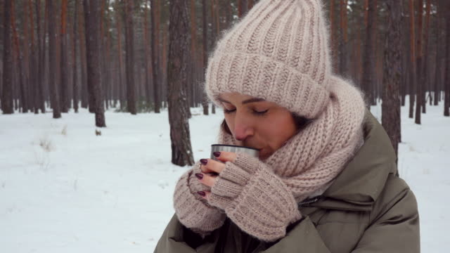 close-up of woman sipping hot tea from mug in the woods - mitten stock videos and b-roll footage