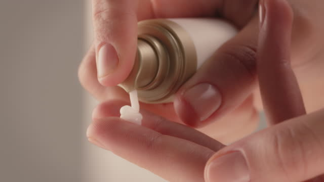 close-up of woman squeezing cream on fingers - human skin stock videos & royalty-free footage