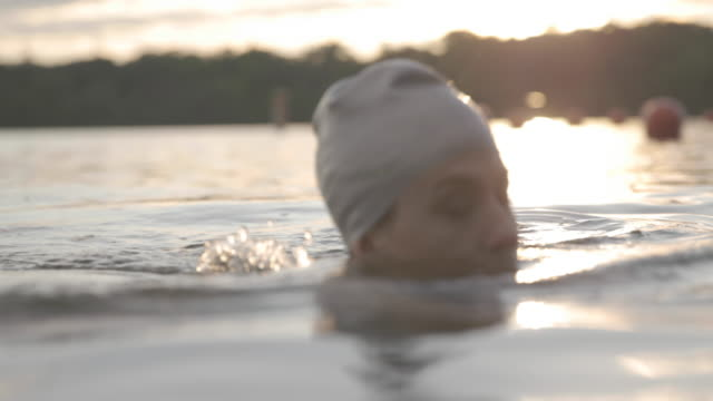 vídeos de stock, filmes e b-roll de close-up of woman swimming in lake - touca de natação