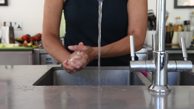 close-up of woman washing her hands in the kitchen sink - kitchen stock videos & royalty-free footage
