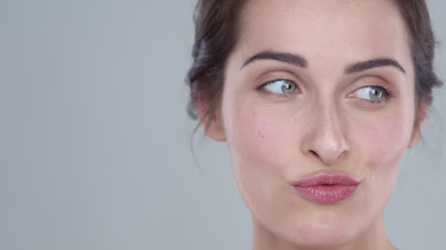 close-up of woman with glowing skin making facial expressions and blowing a kiss to camera - schönheit stock-videos und b-roll-filmmaterial