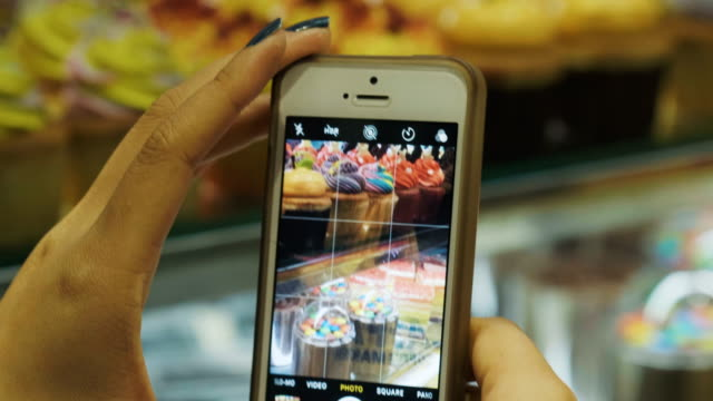 close-up of woman's hand is photographing bakery picture by using smart phone at bakery shop - intrappolato video stock e b–roll
