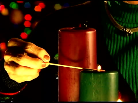 close-up of woman's hand lighting christmas candles  - see other clips from this shoot 1407 stock videos and b-roll footage
