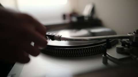 closeup of woman's hand placing the stylus needle on vinyl record - obsolete stock videos & royalty-free footage