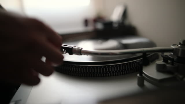 closeup of woman's hand placing the stylus needle on vinyl record - obsoleto video stock e b–roll