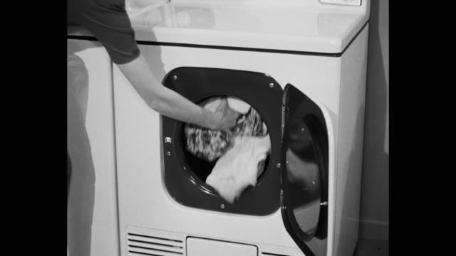 close-up of woman's hand putting clothes in tumble dryer - 1950 video stock e b–roll