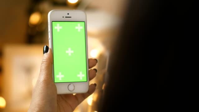 Nahaufnahme von Frauenhand beim Berühren Smartphone mit Chroma Key green-Screen bei ihrem Zimmer-Green Screen Handheld-Smartphone