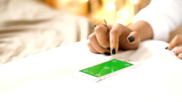 vidéos et rushes de gros plan de la main de la femme alors que vous touchez téléphone intelligent avec écran vert clé de chroma à sa chambre vert écran portable smartphone - seulement des jeunes femmes