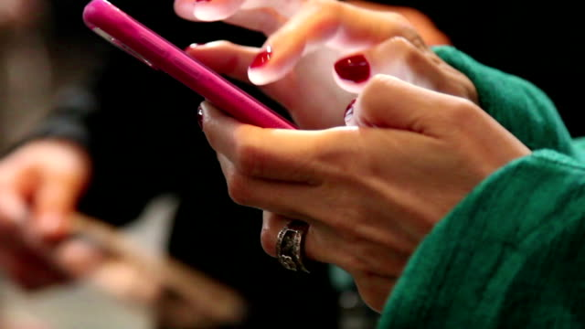 Close-up of woman's hands using app on cell phone.