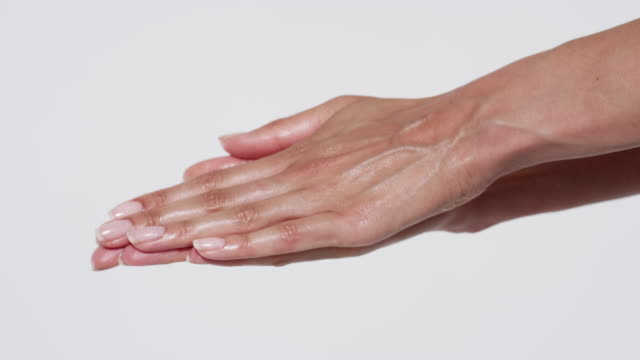 close-up of woman's hands with long, elegant fingers massaging hand cream - applying stock videos & royalty-free footage