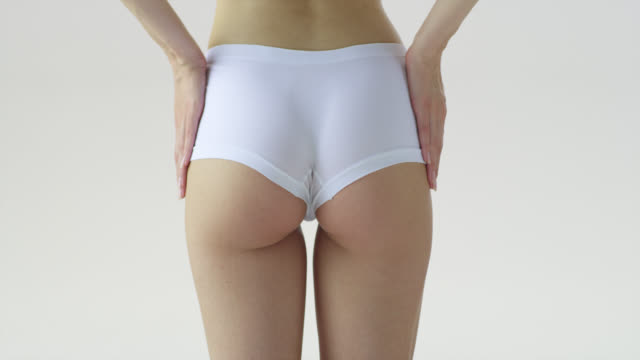 close-up of woman'‎s lower part of the body in white underwear, touching her hips and waist with her hands. - thigh stock videos & royalty-free footage