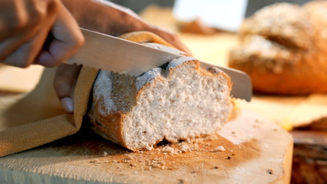 close-up of women hands with a knife cut bread. - spreading stock videos & royalty-free footage