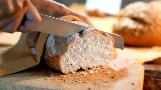 närbild av kvinnor händer med en kniv cut bröd. - smör bildbanksvideor och videomaterial från bakom kulisserna