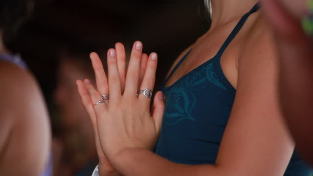 close-up of women's hand in prayer pose and then folding her fingers to hold her hands surrounded by women and with the woman in the background with her eyes closed. - kelly mason videos stock videos & royalty-free footage