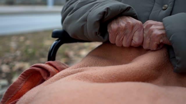 vidéos et rushes de gros plan des mains ridées d'une vieille femme non valide - froid