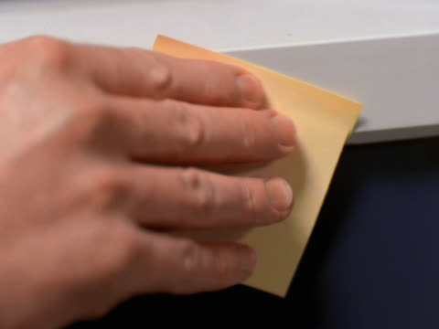 Close-up of yellow post-it being stuck on surface
