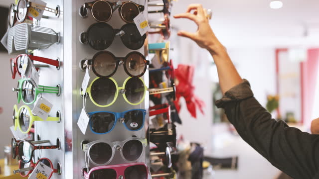 Close-up of young adult shopping for sunglasses